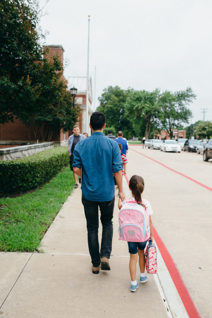 dad walking daughter to first day of school