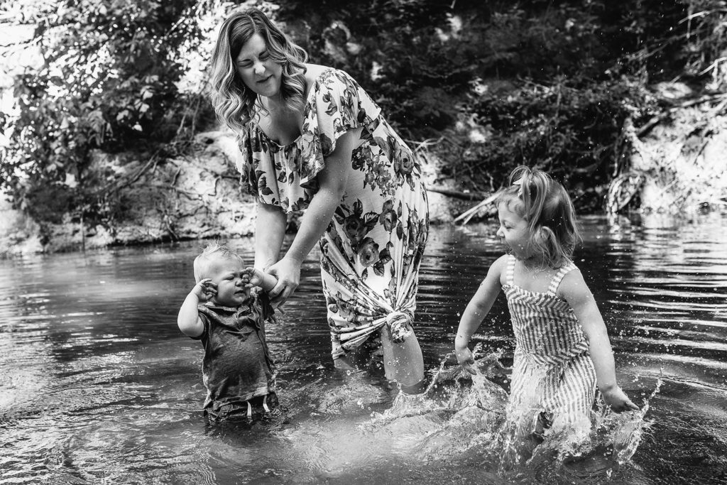 kids splashing in the creek with mommy